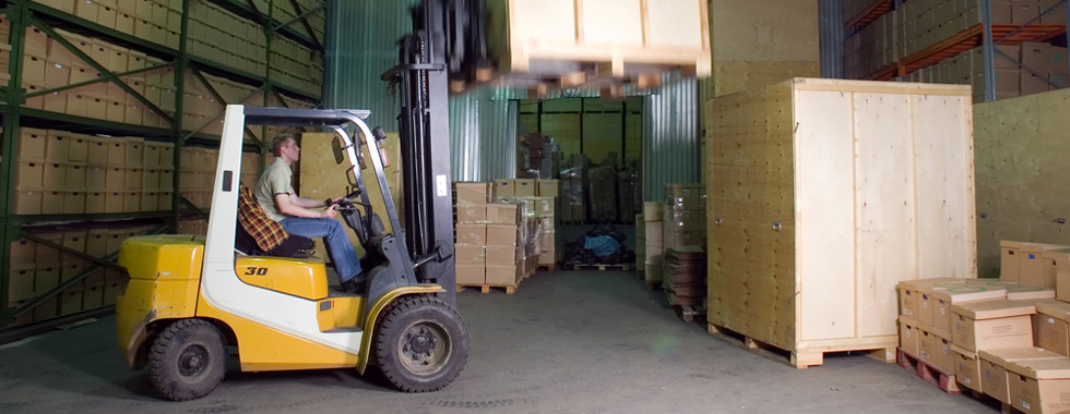 Forklift truck moving boxes in storage warehouse